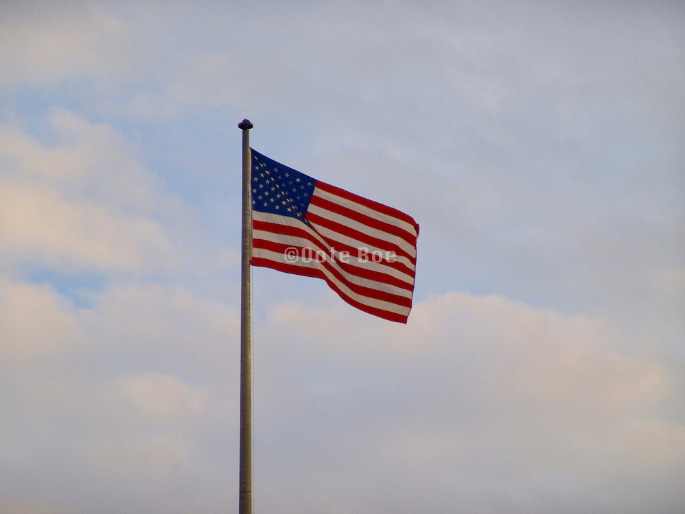 American flag flying against a evening sky