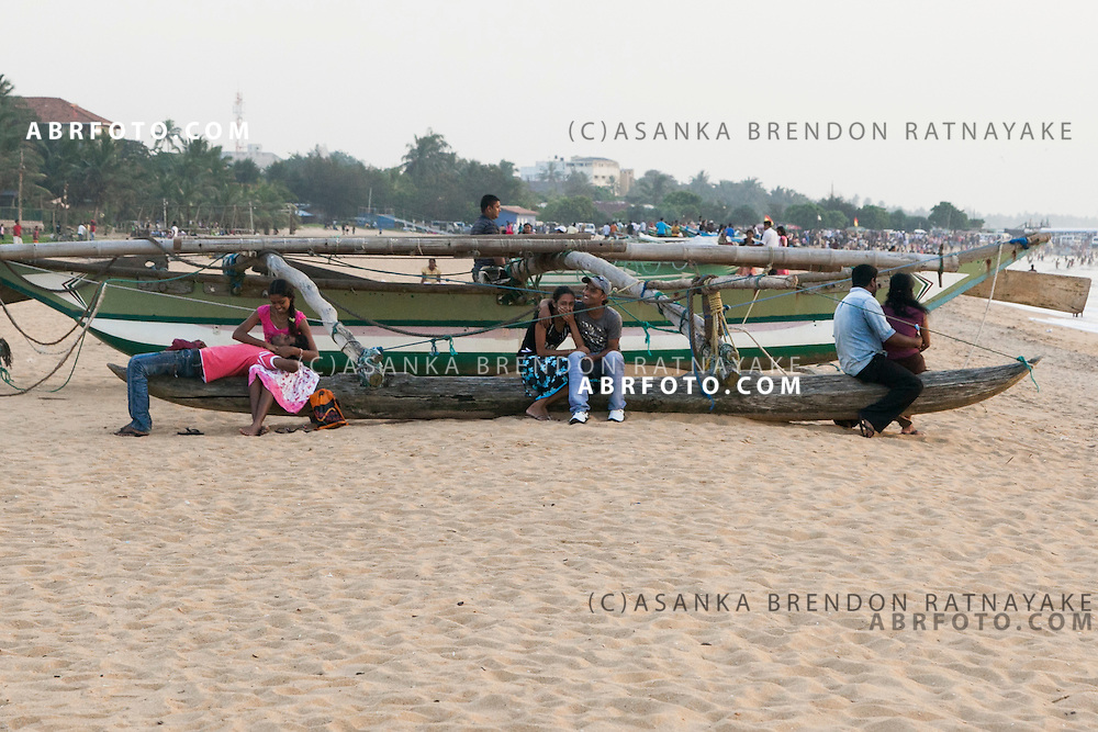 Three young couples relax on a fishing boat which is docked on the sand at Negombo beach.Negombo is a major city in Sri Lanka, located on the west coast of the island and at the mouth of the Negombo Lagoon