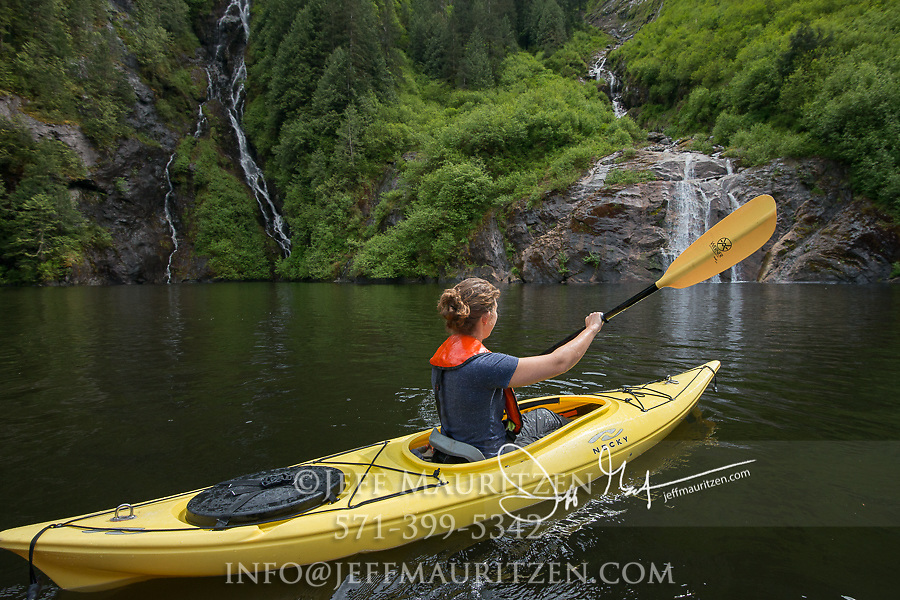 A young woman paddles her kayak near a waterfall at Misty Fiords National Monument, Alaska in springtime.
