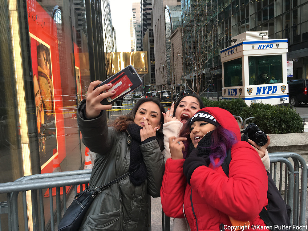 Hispanic women give the finger outside Trump Tower in New York City, expressing their displeasure with President Trump and his policies.