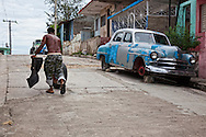 Man rolling a tire up a steep hill past an old car in Santiago de Cuba, Cuba.