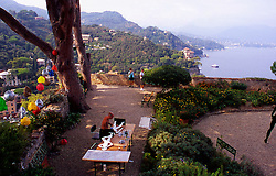 Overhead of harbor with seaside houses and Artist creating Paintings, Italy