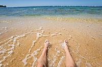 Legs and feet on a beach.  Haena Beach, Kauai, Hawaii.