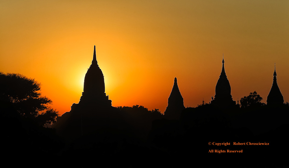 Numerous Buddhist Stupas and Temples are held in silhouette against the golden evening sky, Bagan Myanmar.