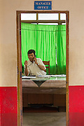 Manager on phone at desk, green curtain, commuter ferry boat Manager Office, Yangon River Jetty