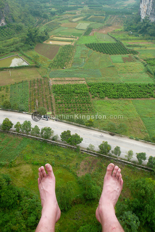 Feet of a rock climber dangling in the air high above a road and farm land near Yangshuo, China (Model Released, Jonathan Kingston)