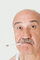 Close-up portrait of senior man with cigarette in mouth over gray background