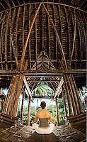 A woman meditates, facing cross-legged away from camera, in the black bamboo Minangkabau Palace of Bambu Indah boutique resort, Bali, Indonesia. Wellness photography by Djuna Ivereigh.