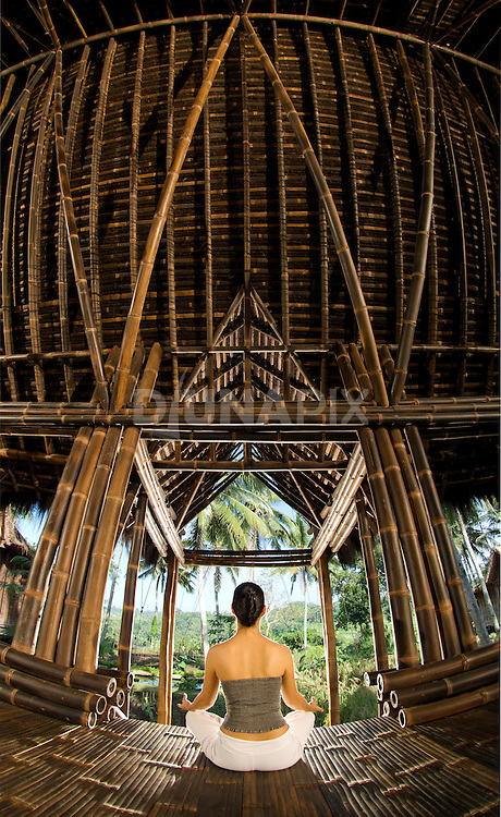 A woman meditates, facing cross-legged away from camera, in the black bamboo Minangkabau Palace of Bambu Indah boutique resort, Bali, Indonesia. Wellness photography by Djuna Ivereigh.