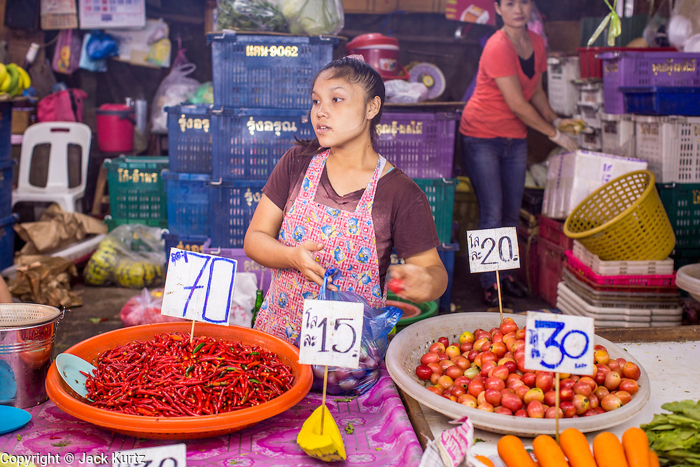 """03 OCTOBER 2012 - BANGKOK, THAILAND:  A woman sells chillies and tomatoes in Khlong Toey Market. Khlong Toey (also called Khlong Toei) Market is one of the largest """"wet markets"""" in Thailand. Thousands of people shop in the sprawling market for fresh fruits and vegetables as well meat, fish and poultry every day.       PHOTO BY JACK KURTZ"""