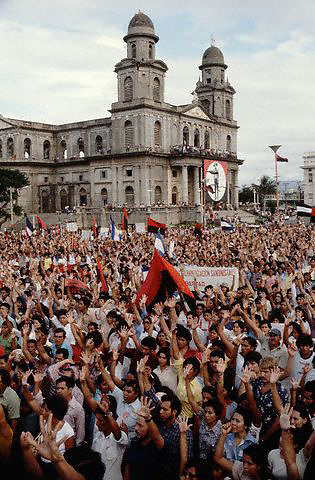 July 1980, Managua, Nicaragua --- Crowds of volunteer teachers take part in a rally for the Nicaraguan Literacy Campaign near a large building. --- Image by © Owen Franken/CORBIS - Photograph by Owen Franken