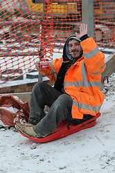 © Licensed to London News Pictures. 18/01/2013.Snow fall makes it too cold to lay bricks so this builder finds time to have a cup of tea a cigarette and a sledge in the snow all at the sametime..Snow fall in the borough of Bromley, South East London over night..Snow in Bromley and across the UK today (18.01.13) as  temperatures stay low..Photo credit : Grant Falvey/LNP