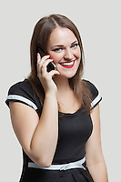 Portrait of young woman communicating on cell phone over gray background