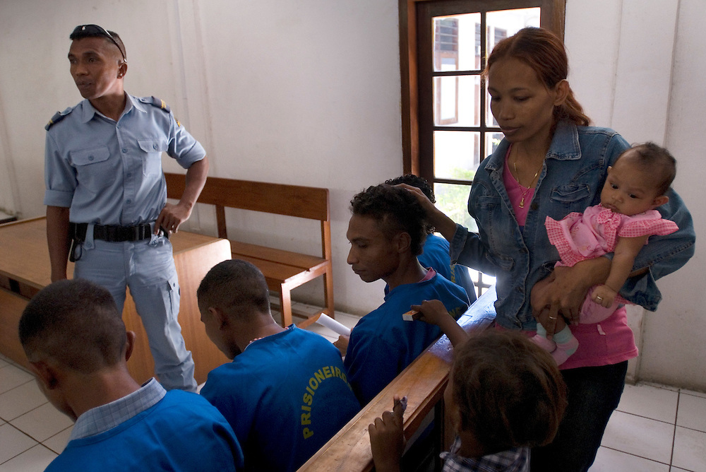 Evidence is heard regarding the arrest of Seven gang leader Sico Valente. His wife and children are shown support by gang members waiting in Dili District Court as they await news of his release.