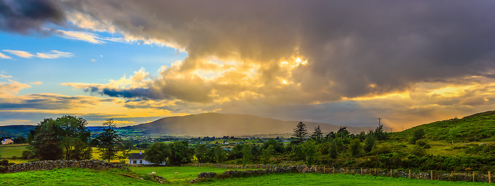 Another one from my trip the other week to capture the rainbow at Flagstaff Viewpoint, I captured this shortly before the rainbow formed looking back in the other direction towards Slieve Gullion. The low evening Sun was just managing to break through the clouds to provide some brilliant orange crepuscular rays and dramatically lit up the sheets of rain falling over the village of Drumintee.<br />