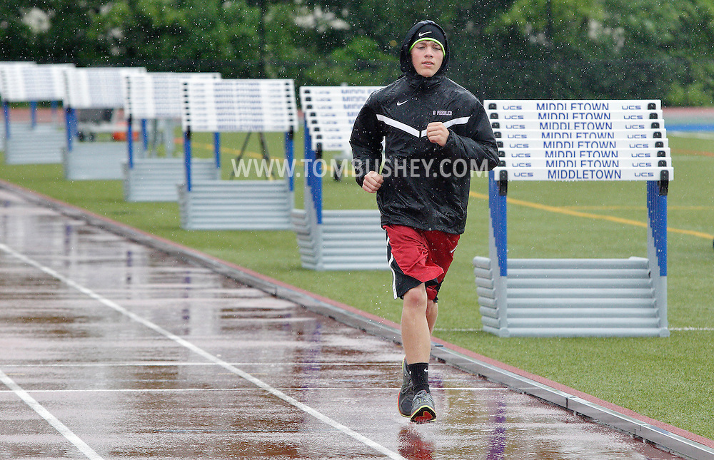 Devan Peebles of South Lewis warms up on the track at Middletown High School after the first day of the state track and field championships was postponed because of the wet weather on Friday, June 7, 2013.