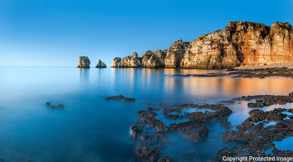 Ponta da Piedade rock formations, view from east in a still Autumn morning. The absence of wind at the sunrise allowed the water of this 7 frames panorama, to be like a mirror.