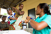 Ramatu Zango holds her 7-month-old daughter Sekinata Sakande (7.7 kg) while discussing with nurse Denise Kalmoni at the Osu Maternity Home in Accra, Ghana on Tuesday June 16, 2009.