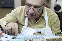 Close-up of a young worker concentrating on repairing jewelry in workshop