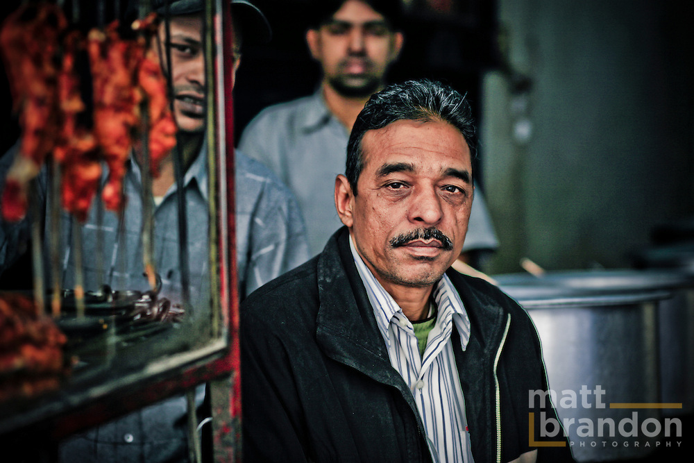 A shopkeeper sits outside his restaurant in Nizamuddin.