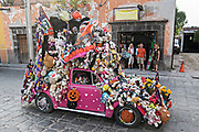 A Volkswagen Beetle art car decorated for Halloween and Dead of the Dead festivals drives down through the expat neighborhood of San Antonio in San Miguel de Allende, Mexico.