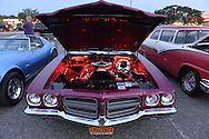 Bellmore, New York, USA. 12th June 2015. Under an open hood, the engine of a red 1972 Pontiac Convertible Le Mans Sport is lit up in red at the Friday Night Car Show held at the Bellmore Long Island Railroad Station Parking Lot. Hundreds of classic, antique, and custom cars were on view at the free weekly show, sponsored by the Chamber of Commerce of the Bellmores.