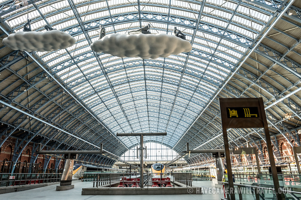 Looking from one end to the other of the distinctive iron and glass arched cover over the platforms of St Pancras Railway Station (now known as St Pancras International). The renovated station features distinctive Victorian architecture and serves as a Eurostar terminal for high-speed trains to Europe. There are also platforms for domestic train services. The distinctive train shed roof was designed by William Henry Barlow.