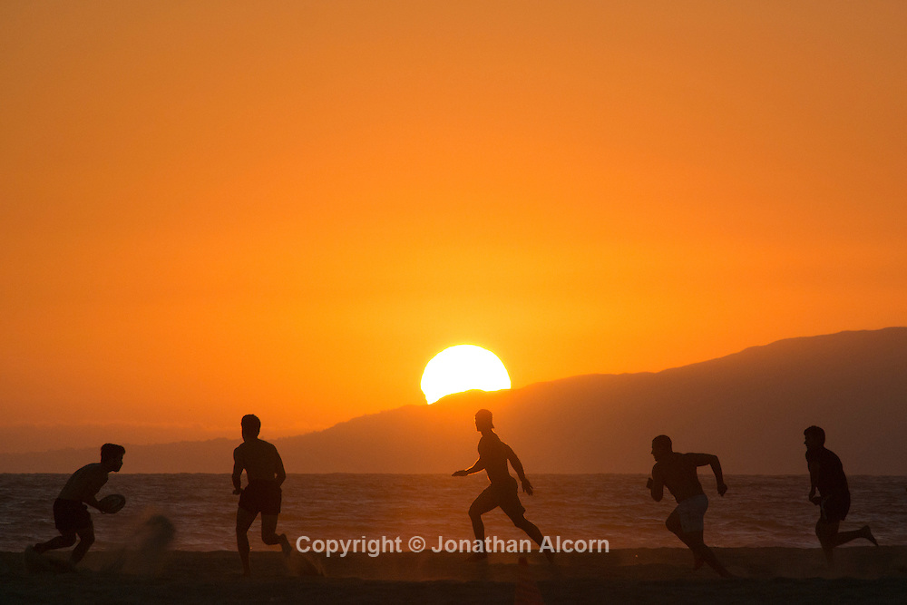 Men play rugby on the beach in Santa Monica as the Sun sets in the distance over the mountains in Malibu