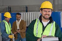Cheerful man standing in factory colleagues in background