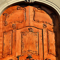 Wooden Door Facing M&uuml;nsterplatz in Basel, Switzerland<br /> This elegant, carved door with inlaid wood is facing the M&uuml;nsterplatz near Basel M&uuml;nster.  The setting sun gave it a rich, amber coloring among the growing shadows.