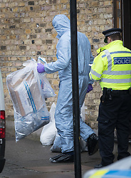 © Licensed to London News Pictures. 21/09/2017. London, UK. A police forensics officer carries evidence in a bag from a house where earlier police and the fire brigade attended and found a burnt body in the garden in Southfields, south London A 40-year-old man and a 34-year-old woman were arrested at the scene on Wednesday, 20 September on suspicion of murder. Photo credit: Peter Macdiarmid/LNP