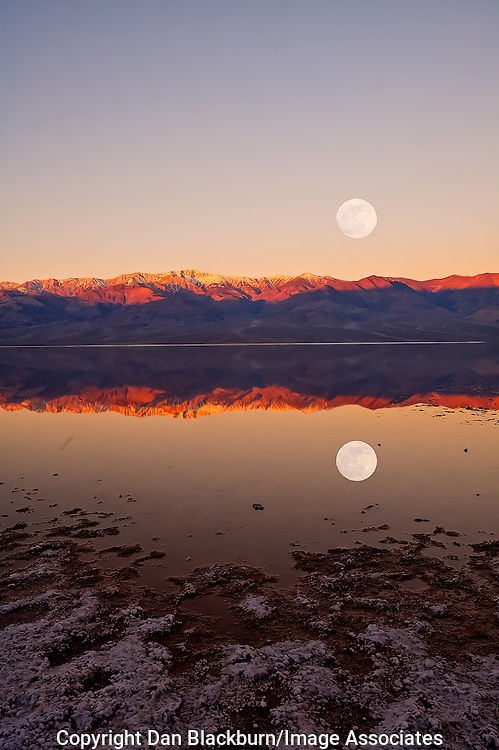 The full moon sets on Telescope Peak in the Panamint Mountains while the sun rises over Badwater in Death Valley, California
