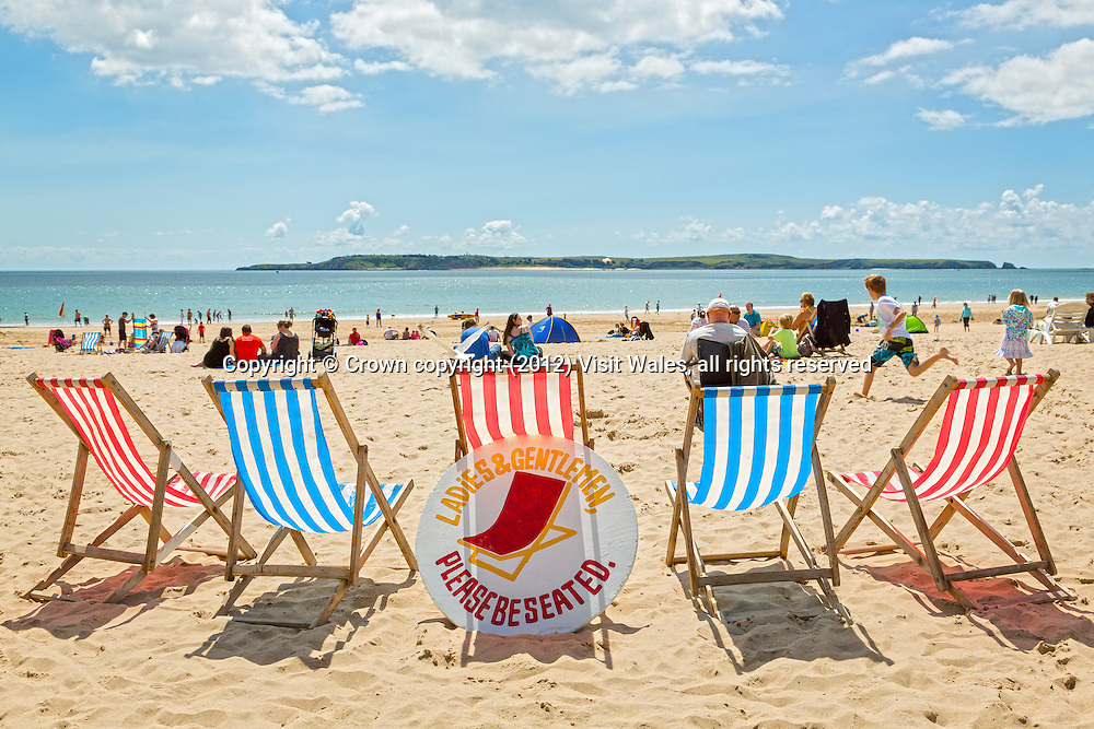 Castle Beach with deck chairs in foreground and Caldey Island in distance<br /> Tenby<br /> Pembrokeshire<br /> South<br /> Towns and Villages