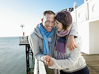 Couple holding hands standing on pier portrait
