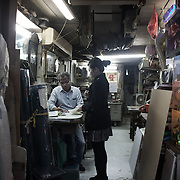 """A woman discusses an order with a shop keeper in Central.<br /> <br /> Hong Kong (香港; """"Fragrant Harbour""""), officially known as Hong Kong Special Administrative Region of the People's Republic of China since the hand-over from the United Kingdom in 1997 under the principle of """"one country, two systsems"""".  7 million people live on 1,104km square, making it the most vertivcal city in the world. Hong Kong is one of the world's leading financial centres along side London and New York, it has one of the highest income per capita in the world as well the moste severe income inequality amongst advanced economies. The Hong Kong civil society is highly regulated but has at the same time one of the most lassiez-faire economies with low taxation and free trade. Civil unrest and political dissent is unusual but in 2014 the Umbrella Movenment took to the streets of Hong Kong demanding democracy and universal suffrage. 93 % are ethnic Chinese, mostly Cantonese speaking."""