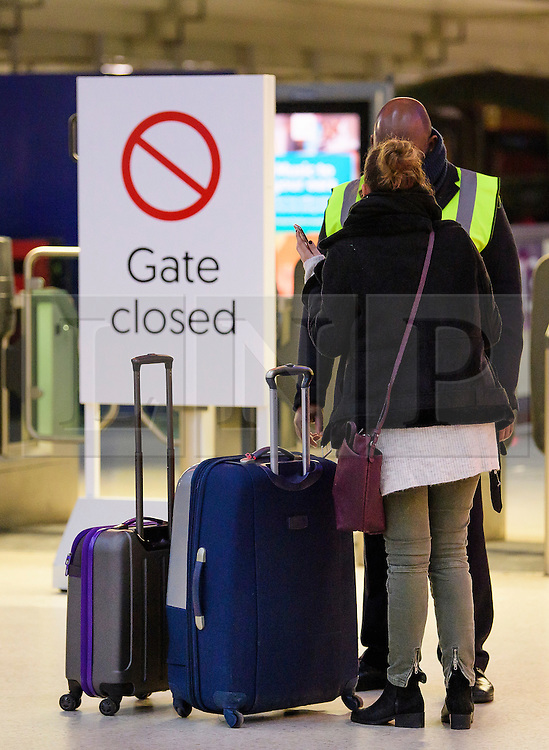 © Licensed to London News Pictures. 14/12/2016. London, UK. A woman pushing luggage is stopped at a closed gate during rush hour at Victoria Station on 14 December 2016, as hundreds of thousands of rail passengers face a second day of a 3 day all-out strike in an escalating dispute over the role of conductors between Southern Rail and the RMT Union. Photo credit: Ben Cawthra/LNP