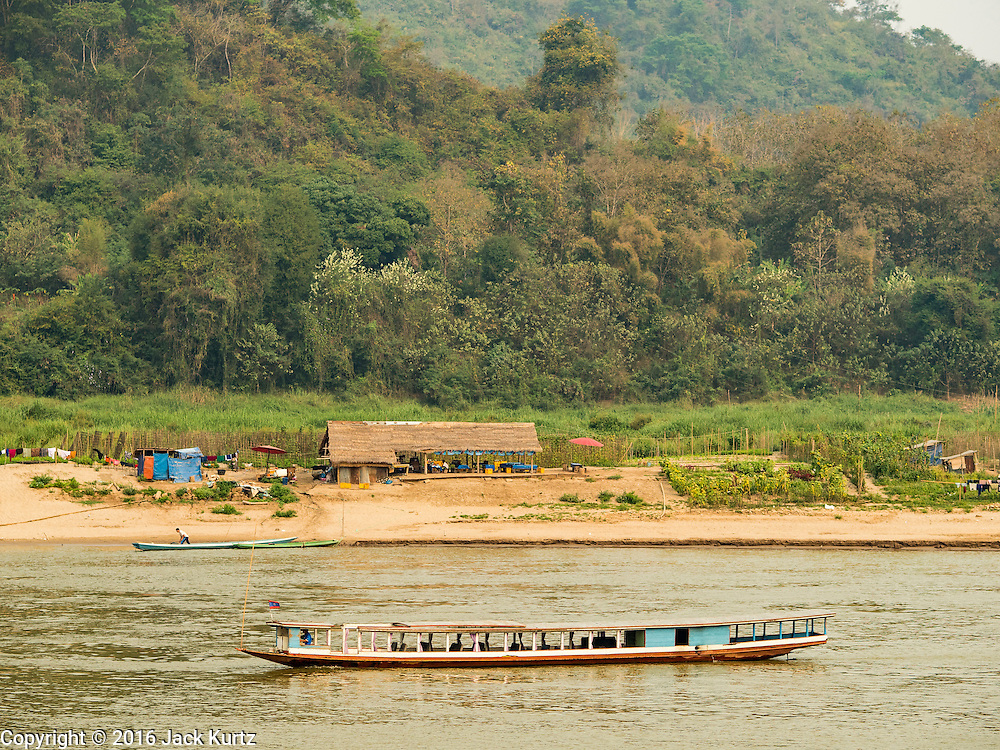 12 MARCH 2016 - LUANG PRABANG, LAOS: A passenger boat goes down the Mekong River near Luang Prabang. Laos is one of the poorest countries in Southeast Asia. Tourism and hydroelectric dams along the rivers that run through the country are driving the legal economy.       PHOTO BY JACK KURTZ