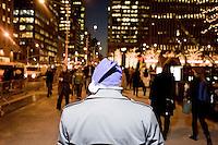 3 Dicembre 2008. New York, NY. Un uomo cammina nella 6th avenue &amp; 49th street indossando una cappello di natale viola appena regalatogli da Fedex. Ogni anno le strade e i negozi di New York City sfoggiano decorazioni natalizie che attraggono turisti da tutto il mondo.<br /> &copy;2008 Gianni Cipriano per Io Donna / Corriere della Sera<br /> cell. +1 646 465 2168 (USA)<br /> cell. +1 328 567 7923 (Italy)<br /> gianni@giannicipriano.com<br /> www.giannicipriano.com