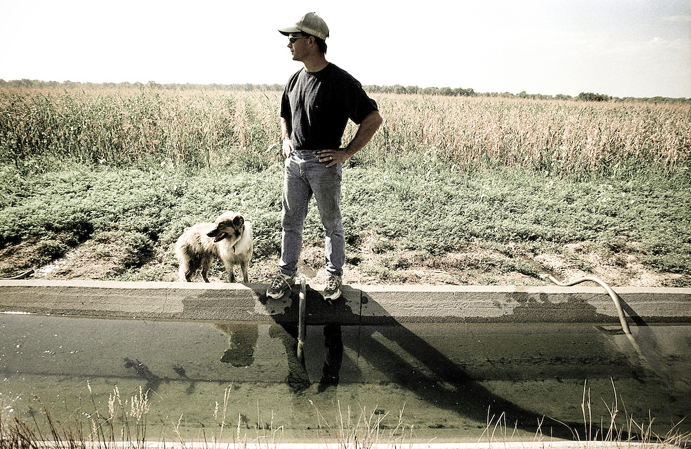 Farmer and his dog checking irrigation ditch