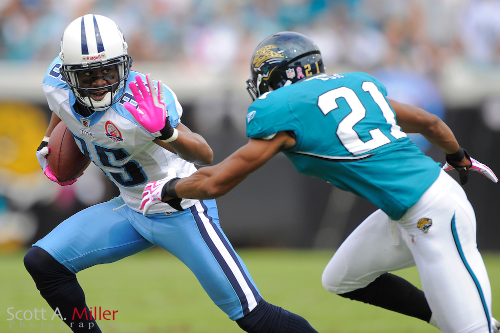 Oct. 4, 2009; Jacksonville, FL, USA; Tennessee Titans wide receiver Nate Washington (85) tries to avoid Jacksonville Jaguars cornerback Derek Cox (21) during the first half of their game at Jacksonville Municipal Stadium. ©2009 Scott A. Miller