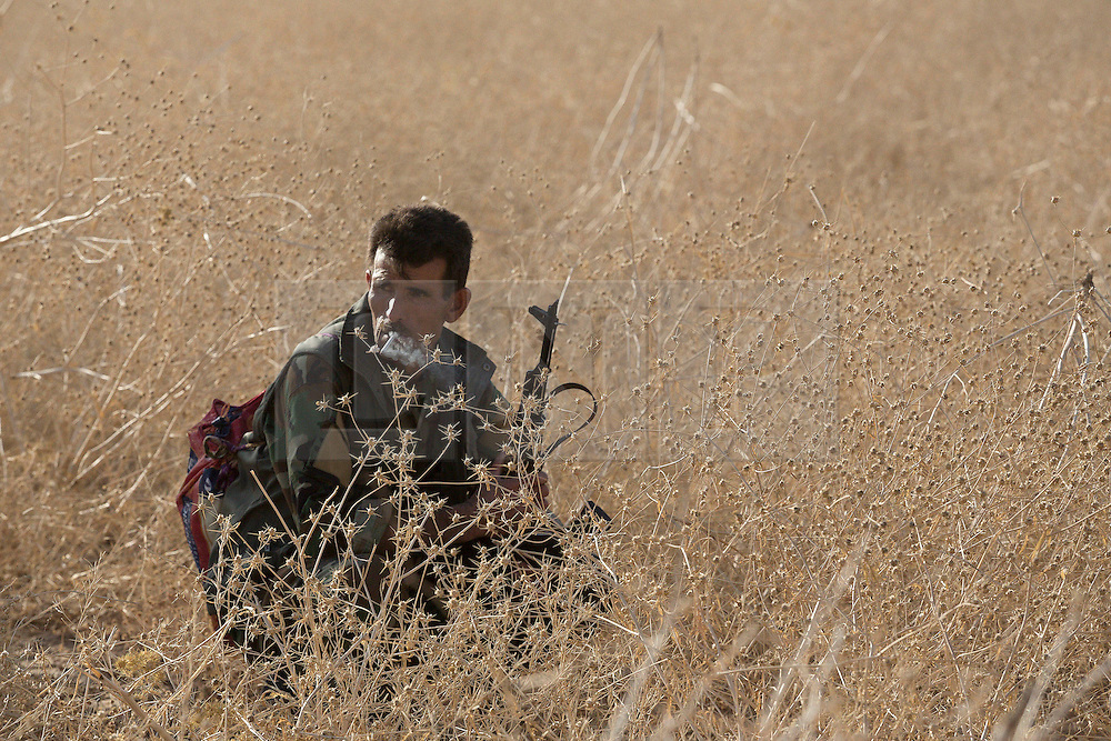 20/10/2016. Bashiqa, Iraq. A peshmerga fighter  takes a cigarette break in a dry field as Kurdish forces launch an offensive to retake the Bashiqa area from Islamic State militants today (20/10/2016).<br />
