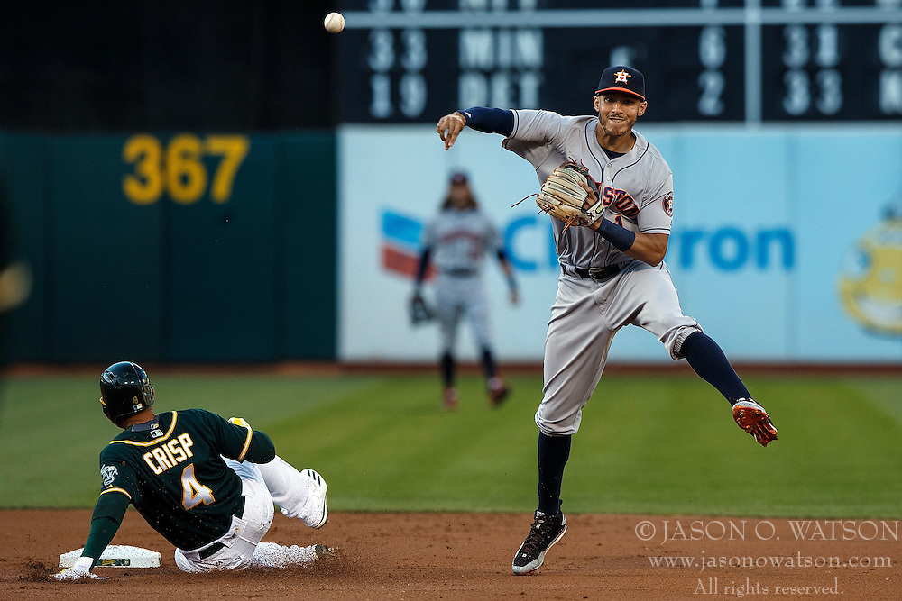 OAKLAND, CA - JULY 19:  Carlos Correa #1 of the Houston Astros completes a double play over Coco Crisp #4 of the Oakland Athletics during the first inning at the Oakland Coliseum on July 19, 2016 in Oakland, California. The Oakland Athletics defeated the Houston Astros 4-3 in 10 innings.  (Photo by Jason O. Watson/Getty Images) *** Local Caption *** Carlos Correa; Coco Crisp