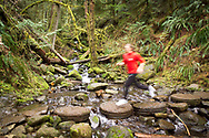 COLUMBIA RIVER GORGE, OR:  A woman runs across a small creek that crosses the Eagle Creek Trail in the Columbia River Gorge, Portland, Oregon.  Trail runners, day hikers, kayakers and other outdoor enthusiasts enjoy the many recreational opportunities that the Columbia River Gorge affords to local residents and tourists alike. (Model Released)