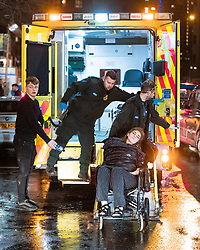 "© Licensed to London News Pictures . 22/12/2018 . Manchester , UK . A woman is carried to an ambulance on a wheelchair , outside Deansgate Locks . Revellers out in Manchester City Centre overnight during "" Mad Friday "" , named for historically being one of the busiest nights of the year for the emergency services in the UK . Photo credit : Joel Goodman/LNP"