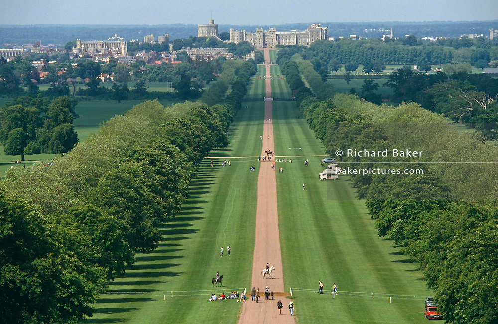 From a high viewpoint on Snow Hill, we see the green  'Long Walk' in the Royal Estate's Windsor Great Park. We look down the 3-mile straight road into the distance towards Windsor Castle in the summer shinshine during the equestrian 3-Day Event held annually on Her Majesty the Queens's property. Half-way down the lush avenue of Elm trees there are some horses and their riders either warming up before competition, or galloping across the landscape on a round against the clock. A few spectators have stopped to watch this part of the course but others are elsewhere at the dramatic water jumps. The Long Walk was commenced by Charles II from 1680-1685 by planting a double avenue of elm trees. The central carriage road was added by Queen Anne in 1710. Windsor Castle was begun in the 11th century by William the Conqueror as it afforded a good defensive point over the River Thames. A vast area of Windsor Forest to the south of the castle became reserved by the King for personal hunting and also to supply the castle with wood, deer, boar and fish. Windsor Great Park (locally referred to simply as the Great Park) is a large deer park and Crown Estate of 5,000 acres, to the south of the town of Windsor on the border of Berkshire and Surrey in England. The park was, for many centuries, the private hunting ground of Windsor Castle and dates primarily from the mid-13th century. Now largely open to the public, the parkland is a popular recreation area for residents of the western London suburbs.