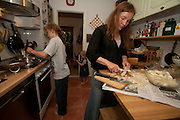 Astrid Holmann of the Hollmann Sturm family in Hamburg, Germany with her daughter Lillith Sturm,  and son, Malte Erik at the stove. Preparing white asparagus for supper. They were photographed for the Hungry Planet: What I Eat project with a week's worth of food in June. Model Released.