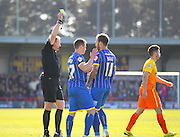 Referee Trevor Kettle shows a yellow card to AFC Wimbledon Sean Rigg during the Sky Bet League 2 match between AFC Wimbledon and Wycombe Wanderers at the Cherry Red Records Stadium, Kingston, England on 18 April 2015. Photo by Phil Duncan.