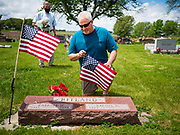 25 MAY 2020 - ROLAND, IOWA: SCOTT RITLAND places an American flag on his father's grave in Roland Cemetery, in Roland, Iowa, a farming community an hour north of Des Moines. In 2020, most public Memorial Day events in Iowa were canceled because of the COVID-19 pandemic, but some families, including the Ritlands, had their own private events. Memorial Day is a federal holiday to honori and mourn the military personnel who have died while serving in the United States Armed Forces. Memorial Day is observed on the last Monday in May.        PHOTO BY JACK KURTZ