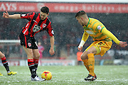 Morecambe Striker Shaun Miller battles with Yeovil Defender Yakub Sokolik during the Sky Bet League 2 match between Morecambe and Yeovil Town at the Globe Arena, Morecambe, England on 16 January 2016. Photo by Pete Burns.