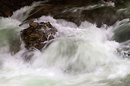Water cascades around rocks on the Little Qualicum River in Little Qualicum Falls Provincial Park on Vancouver Island, British Columbia, Canada